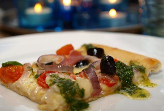 Image: Pizza med parmaskinke, mozzarella, tomater, løk, oliven, parmesan og basilikumolje